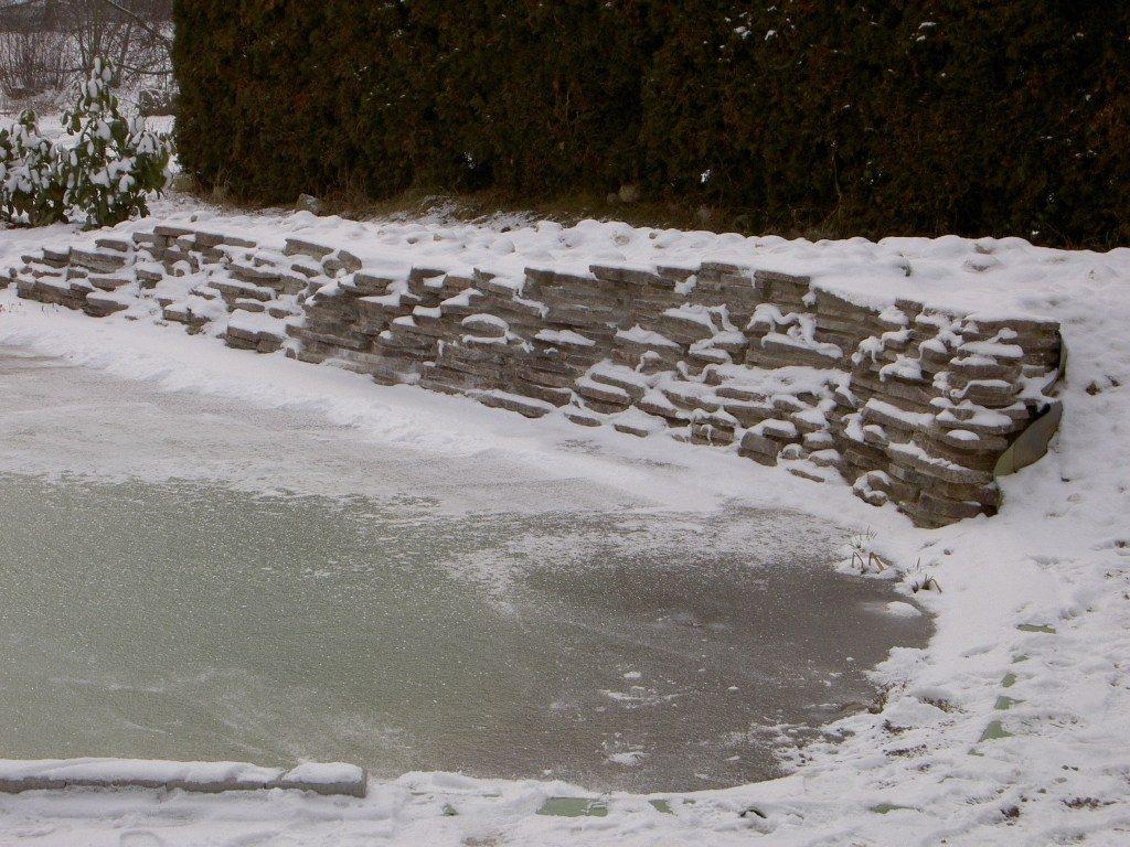 Zugefrorener Teich mit Mauer