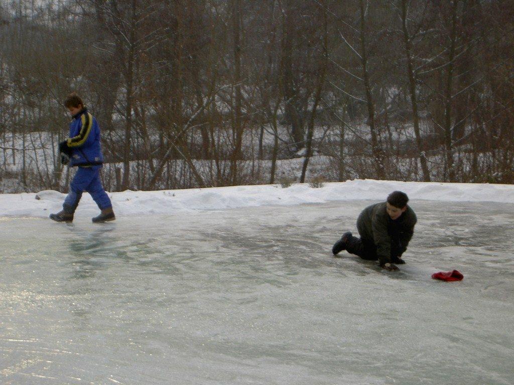 Schlitterspaß auf zugefrorenem Teich